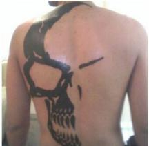 Half skull tattoo on the whole body and back in black.JPG