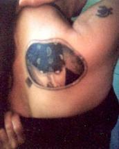 Very unique tattoo of a round window with a guy inside.JPG