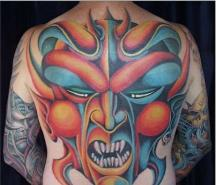 Big evil face tattoo in colors on the whole back.JPG
