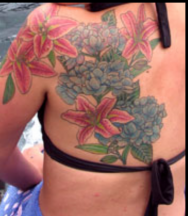 Hawaiian back tattoo with full of tropical flowers photo.PNG