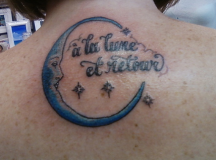 Moon and letters tattoos on the upper back.PNG